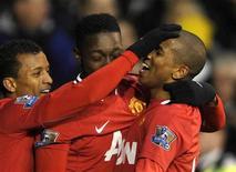 """Футболисты """"Манчестер Юнайтед"""" поздравляют Эшли Янга  с голом, забитым в игре против """"Тоттенхэма"""" в Лондоне, 4 марта 2012 года. Дубль Эшли Янга помог """"Манчестер Юнайтед"""" добиться в воскресенье победы над лондонским """"Тоттенхэмом"""" со счетом 3-1 и вновь расположиться на расстоянии двух очков позади """"Манчестер Сити"""", обыгравшего в субботу """"Болтон"""" 2-0. REUTERS/Dylan Martinez"""