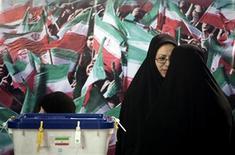 Предствительницы избирательной комиссии стоят около урн на участке в Тегеране, 2 марта 2012 года. Сторонники религиозного лидера Ирана аятоллы Али Хаменеи, по предварительным подсчетам, получили наибольшее число мест в парламенте в ходе выборов, прошедших в стране в минувшую пятницу. REUTERS/Morteza Nikoubazl