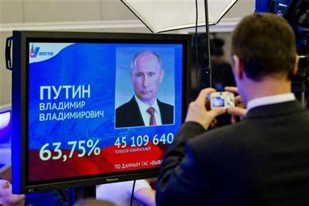 A man takes a picture of a screen showing the preliminary results of Russian Prime Minister Vladimir Putin in the presidential election at the building of the Central Election Commission in Moscow, March 5, 2012. REUTERS/Thomas Peter