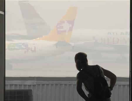 A passenger looks at airplanes shrouded in heavy smog, caused by peat fires in nearby forests, at Vnukovo airport outside Moscow, August 9, 2010. REUTERS/Alexander Natruskin