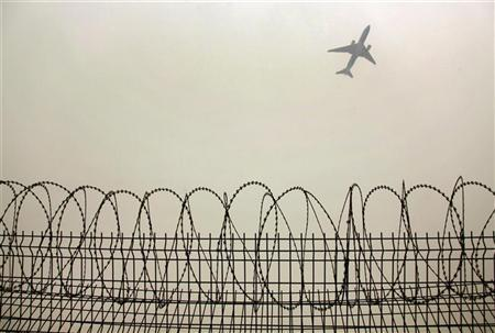 A plane flies in the polluted air above the airport fences in Beijing February 22, 2012.  REUTERS/Petar Kujundzic