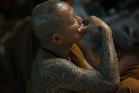 A Buddhist monk is seen with tattoos on his body at Wat Bang Phra in Nakhon Prathom province, about 80 km (50 miles) from Bangkok Picture taken March 2, 2012. REUTERS/Sukree Sukplang