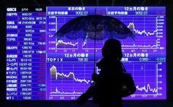 Женщина идет мимо электронного котировочного табло в Токио, 14 февраля 2012 г. Фондовые рынки Азии снизились в понедельник из-за опасений по поводу замедления китайской экономики. REUTERS/Toru Hanai