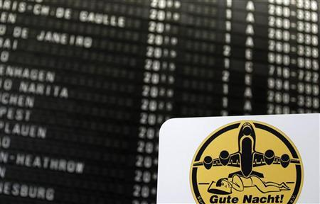A placard is seen in front of a flight schedule board as protesters take part in a demonstration against a new landing track and flight noise at Frankfurt's Fraport airport January 16, 2012.  REUTERS/Kai Pfaffenbach