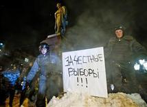 """Полиция зачищает от митингующих фонтан на Пушкинской площади 5 марта 2012 года. Сотни протестующих, включая оппозиционеров Алексея Навального и Сергея Удальцова, были задержаны на акциях протеста в двух столицах на следующий день после победы Владимира Путина на президентских выборах, которые власть сочла """"чистыми"""", а наблюдатели и оппозиция - нечестными. REUTERS/Thomas Peter"""