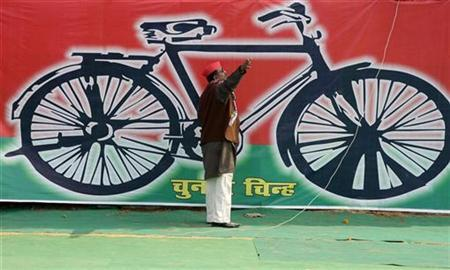 A Samajwadi Party worker gestures in front of a banner with the party's electoral symbol, the bicycle, in Allahabad January 31, 2012. REUTERS/Jitendra Prakash/Files