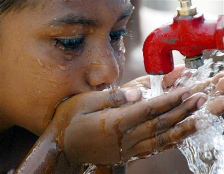 A street child drinks water from a tap in a slum area of New Delhi June 4, 2003 to quench his thirst during a heat wave.