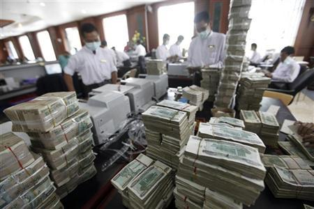 Cashiers are seen behind piles of kyat banknotes as they count it in a private bank in Yangon July 21, 2011.   REUTERS/Soe Zeya Tun