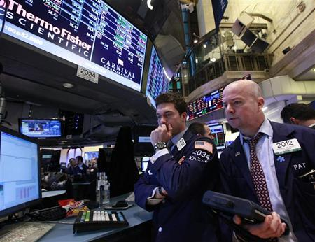 Specialist trader Joseph Dreyer (L) of Knight Capital works at the post that trades Carnival Cruise lines on the floor of the New York Stock Exchange, February 28, 2012. REUTERS/Brendan McDermid