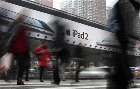 People walk past an Apple billboard advertising the iPad 2 in downtown Shanghai March 1, 2012. REUTERS/Carlos Barria
