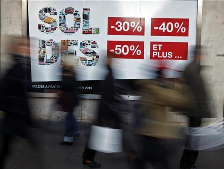 Shoppers walk past a clothing store window advertising sales in Nice, southeastern France, January 11, 2012 during the first day of the winter sales.     REUTERS/Eric Gaillard