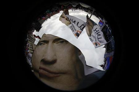 Supporters of Russian Prime Minister Vladimir Putin wave flags in a picture taken with a fisheye lens before a rally in central Moscow March 5, 2012. REUTERS/Pawel Kopczynski