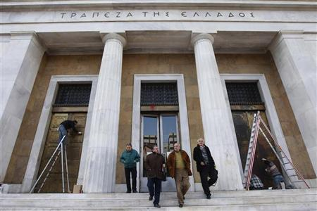 People leave the Bank of Greece as cleaning works are in progress, in central Athens March 6, 2012. Greece has no plans to extend the March 8 deadline on its bond swap offer to private creditors, Greek officials said on Tuesday, dismissing market rumours that the cutoff date may be put back to increase participation in the offer.   REUTERS/John Kolesidis