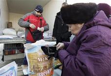 Пенсионерка покупает муку на рынке в Ставрополе 22 января 2011 года. Индекс потребительских цен в РФ с 28 февраля по 5 марта 2012 года вырос на 0,1 процента, показав с начала года рост на 1,0 процента, сообщил Росстат в среду. REUTERS/Eduard Korniyenko