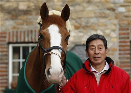 Japanese dressage rider Hiroshi Hoketsu poses with his horse Whisper at his stable in Aachen March 6, 2012. REUTERS/Ina Fassbender