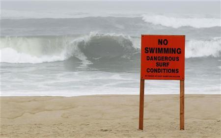 A warning sign is seen on a public beach as Hurricane Irene approaches Long Island in East Hampton Village, New York August 27, 2011.  REUTERS/Lucas Jackson