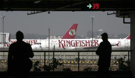 Airport staff are silhouetted as Kingfisher Airlines' aircraft is seen parked at the airport in New Delhi February 21, 2012. REUTERS/Parivartan Sharma