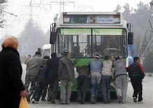 Люди толкают обесточенный троллейбус в Душанбе во время перебоев с электричеством 28 ноября 2006. Таджикистан после двухлетней паузы вновь последовал рецепту международных финансовых организации о повышении стоимости электроэнергии, но ее удорожание, сразу на 22 процента, для населения чревато усилением недовольства в беднейшей стране Средней Азии, говорят аналитики. REUTERS/Nozim Kalandarov