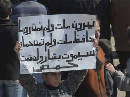A boy holds up a placard during a demonstration against Syria's President Bashar Al-Assad in the town of Hula near the city of Homs March 2, 2012. The placard reads: ''Nero died, Rome did not die, Hafez died, Hama did not die, Bashar will die, Homs will not die''. REUTERS/Handout