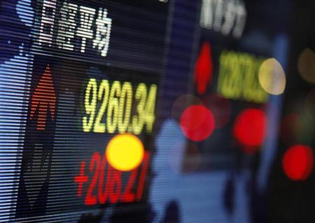 Japan's benchmark Nikkei share average is displayed on an electronic board outside a brokerage in Tokyo February 15, 2012. REUTERS/Yuriko Nakao