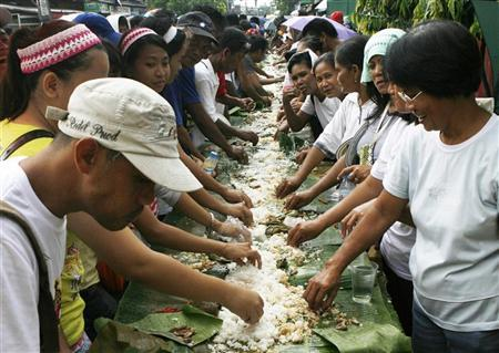 Residents eat lunch along the busy streets of Taguig city, east of Manila July 26, 2009 to try to set a record by having a boodle fight stretching over tables more than 2 km long. REUTERS/Romeo Ranoco/Files