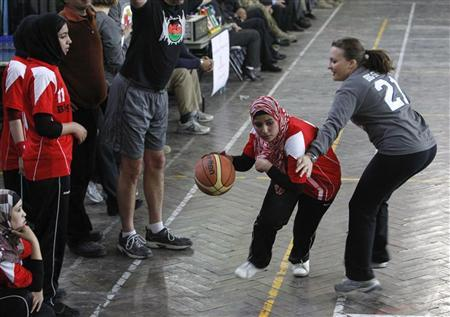 Players from the Afghan Women's Olympic Basketball Team (in red), the International Security Assistance Forces (ISAF) and the United States Embassy Kabul compete in a women's basketball exhibition game to mark International Women's Day, at the ISAF headquarters in Kabul March 7, 2012. REUTERS/Omar Sobhani