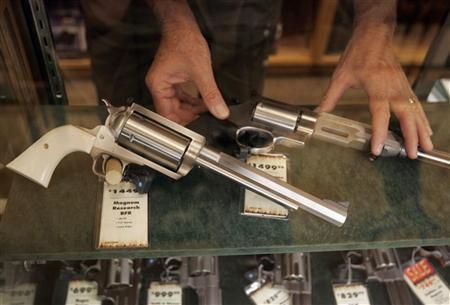 A salesman takes a gun out of the display case at the Cabela's store in Fort Worth, Texas June 26, 2008. REUTERS/Jessica Rinaldi