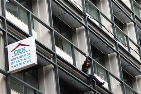 Lambrousi Harikleia, an employee of the Workers Housing Organisation threatens to jump from the office where she worked because her wage has been cut and she and her husband were threatened with layoffs, in Athens February 15, 2012. REUTERS/Panayiotis Tzamaros