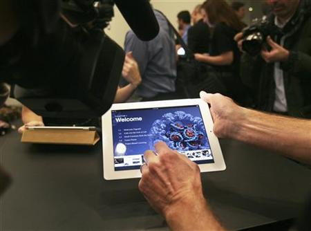 A man shows an example of an iBook textbook on an iPad after a news conference introducing a digital textbook service in New York January 19, 2012. Apple Inc unveiled a new digital textbook service called iBooks 2 on Thursday, aiming to revitalize the U.S. education market and quicken the adoption of its market-leading iPad in that sector. During the event, Apple also introduced tools to craft digital textbooks and demonstrated how authors and even teachers can create books for students. REUTERS/Shannon Stapleton