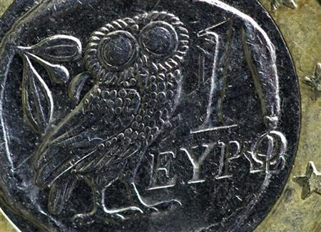 An owl, copied from an ancient Athenian 4 drachma coin, is seen on the face of a worn standard one-Euro coin issued in Greece in this illustration taken in Paris February 15, 2012. REUTERS/Mal Langsdon