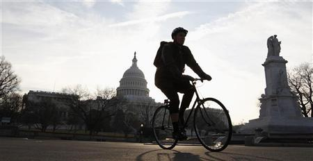 A cyclist passes the Capitol in Washington February 17, 2012. A deal to renew a payroll tax cut for 160 million U.S. workers through 2012 headed toward congressional approval as Democratic and Republican leaders rallied support for the bipartisan agreement. REUTERS/Kevin Lamarque