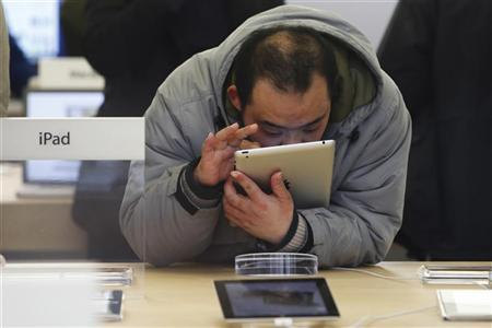 A customer tests out an Apple iPad at an Apple Store in downtown Shanghai March 1, 2012. REUTERS/Aly Song