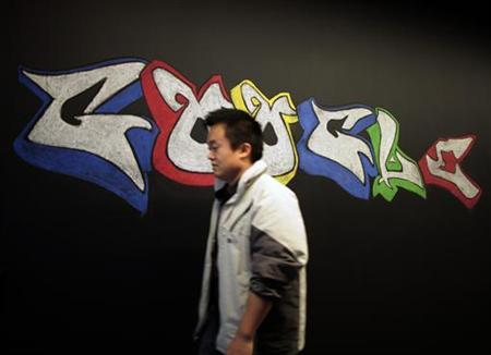 A man walks past a Google logo drawn with chalk on a wall at the Google campus near Venice Beach, in Los Angeles, California January 13, 2012. REUTERS/Lucy Nicholson/Files