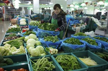 A vendor waits for customers at her vegetable stall at a market in Shanghai February 9, 2012. REUTERS/Aly Song/Files