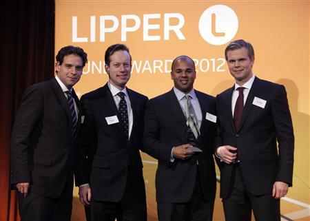 Brian Ford (L), Charles Lahr (2nd from L), and Mauricio Machado (2nd from R) of PIMCO Real Return Asset Fund stand with Lars Asplund, Managing Director of Lipper, as they are presented the award for Best Large Size Equity Firm at the Thomson Reuters Lipper Awards ceremony, in New York, March 8, 2012. REUTERS/Chip East