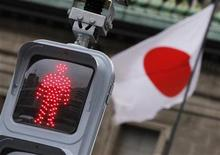 """A """"Don't Walk"""" traffic signal is seen in front of the national flag hoisted on the headquarters of Bank of Japan in Tokyo February 8, 2012. REUTERS/Kim Kyung-Hoon"""