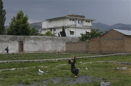 Resident boy Adeel, 8, plays with a tennis ball in front of the compound where U.S. Navy SEAL commandos reportedly killed al Qaeda leader Osama bin Laden in Abbottabad May 5, 2011. REUTERS/Akhtar Soomro