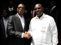 Senegalese singer Youssou N'dour shakes hands with opposition leader Macky Sall (R) during a news conference in central Dakar March 1, 2012. REUTERS/Youssef Boudlal