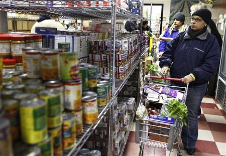 A woman looks at canned food items at the Food Bank For New York City Community Kitchen & Food Pantry of West Harlem in New York December 21, 2010. REUTERS/Shannon Stapleton