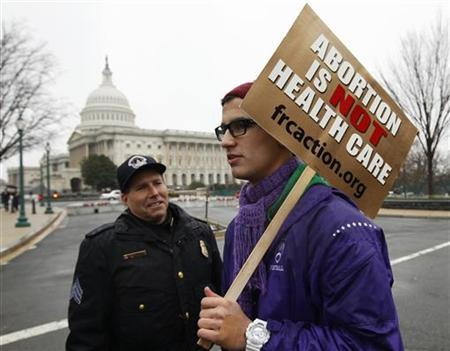 An anti-abortion demonstrator passes the U.S. Capitol as he takes part in the ''March for Life'' in Washington January 23, 2012. REUTERS/Kevin Lamarque