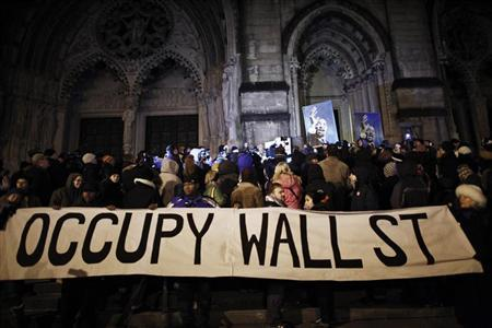 Occupy Wall Street members gather at the Cathedral Church of Saint John the Divine to march during a candlelight vigil to honor Rev. Martin Luther King, Jr. in New York January 15, 2012. REUTERS/Eduardo Munoz
