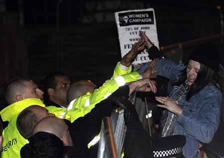 Security guards prevent a student from climbing a fence into the Cambridge Union Society compound in central England March 9, 2012. Dominique Strauss-Kahn, the former IMF head who was accused of sexual assault in the U.S., spoke at the Cambridge Union on Friday. REUTERS/Paul Hackett