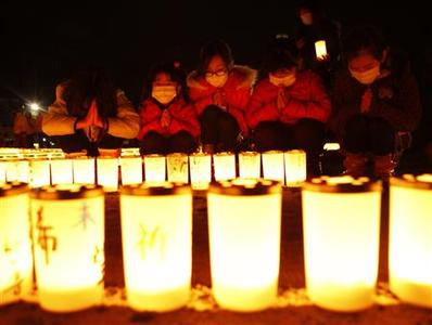 Girls pray after arranging candles at a candlelight event in Iwaki, Fukushima prefecture March 10, 2012. REUTERS/Kim Kyung-Hoon