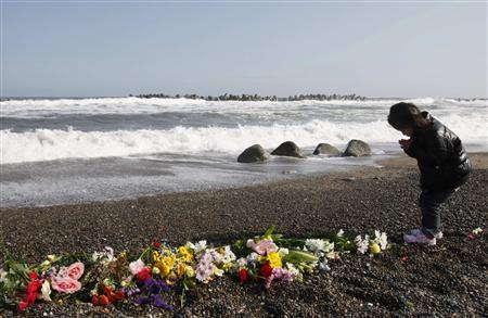 A girl offers prayers for victims of the March 11, 2011 earthquake and tsunami at a seaside which was damaged by the disaster in Iwaki, Fukushima prefecture March 11, 2012, to mark the first anniversary of the earthquake and tsunami that killed thousands and set off a nuclear crisis. REUTERS/Kim Kyung-Hoon
