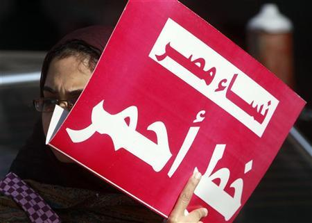 A woman holds a sign that reads ''Egypt women red line'' as they protest against military council violations and virginity tests against females outside the State Council court and in support of Samira Ibrahim in Cairo, December 27, 2011. REUTERS/Amr Abdallah Dalsh