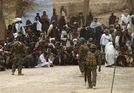 Afghan National Army soldiers keep watch as Afghans gather outside a U.S. base in Panjwai district Kandahar province, March 11, 2012. REUTERS/Ahmad Nadeem