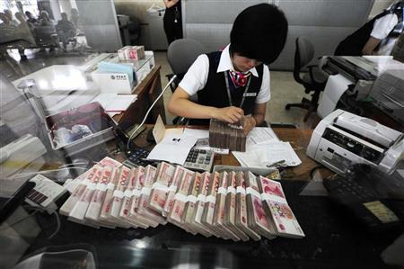 An clerk counts yuan banknotes at a bank in Hefei, Anhui province, June 20, 2010. REUTERS/Stringer/Files