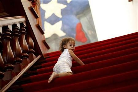 A refugee girl climbs up a staircase at foreign minister headquarters in Caracas February 11, 2011. REUTERS/Jorge Silva