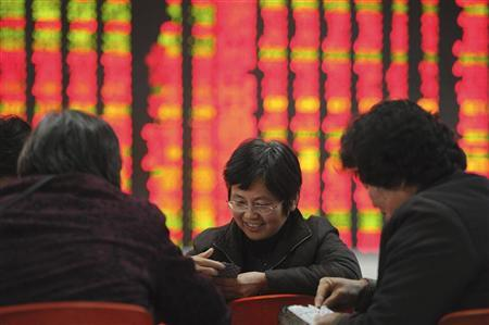 Investors play cards in front of an electronic board showing stock information at a brokerage house in Hefei, Anhui province January 4, 2011. REUTERS/Stringer