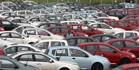 An employee stands amid cars at the stockyard of the General Motors India Ltd. plant at Halol, about 150 east of Ahmedabad August 28, 2009. REUTERS/Amit Dave/Files
